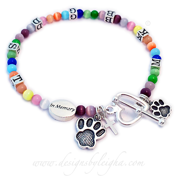 Rainbow Bridge in Memory Bracelet with an In Memory charm and the initials of her pets that have crossed the Rainbow Bridge. M K B G D S T on the bracelet. She upgraded to the Heart Toggle Clasp and added 3 charms. A Medium Paw Print charm, a Small Paw Print Charm and a Tiny Cross charm.