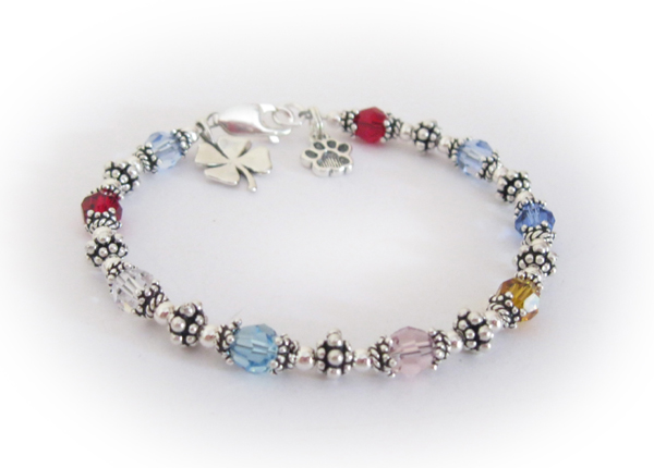 This bracelet is shown with 9 birthstone crystals a shamrock charm and a paw print charm