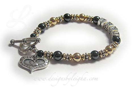 DBL-H3-1 string bracelet   Enter: TASI This 1-string Hematite and Gold Mother Bracelet with 1 name. They added a Heart within a Heart charm and upgraded the clasp to a Heavy Heart Toggle.