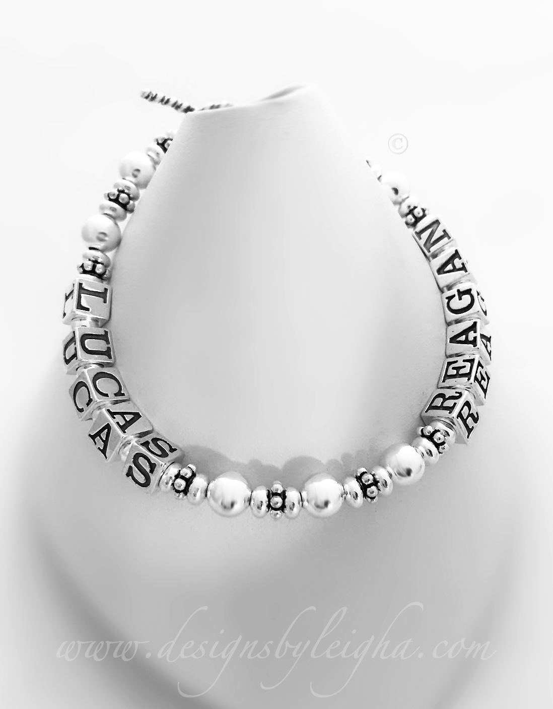This is a 1 string with 2 names all sterling silver mother bracelet with Lucas and Reagan and no crystals.